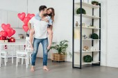 Photo young man giving piggyback ride to smiling girlfriend in furnished room with st valentine day decoration
