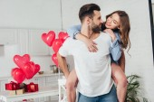 young man giving piggyback ride to smiling girlfriend at home with st valentine day decoration
