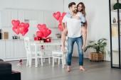 šťastný pár vezou doma v zařízeném pokoji s balónky ve tvaru srdce na pozadí