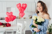 Photo selective focus of a smiling girl holding bouquet of flowers in room decorated with heart-shaped balloons
