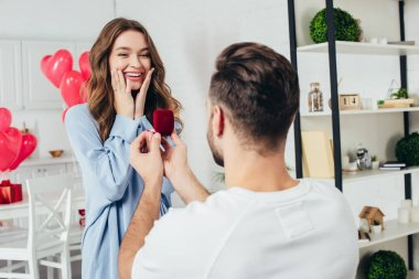back view of man doing proposal at valentines day to girlfriend