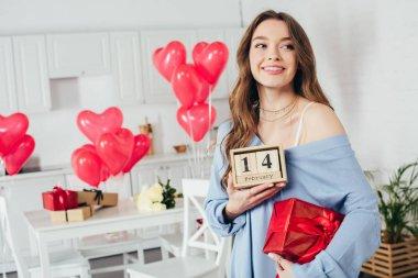 hediye kutusu ve ahşap takvim ile st Sevgililer günü tarihi evde tutan mutlu gülümseyen kız