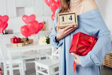 Kırpılan hediye kutusu ve ahşap takvim ile st Sevgililer günü tarihi evde tutan kız görünümünü