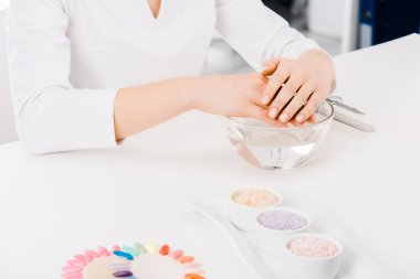 Cropped shot of manicurist in white uniform sitting at workplace
