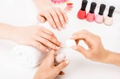 Photo Girl holding hands on towel while manicurist applying nail polish