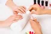 Fotografie Oříznutý pohled dívka s krátké nehty, drželi se za ruce na ručník a manikérka použití lak na nehty