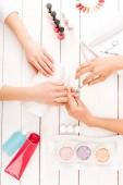 Fotografia Vista parziale del manicure utilizzando tagliaunghie mentre si lavora con il cliente