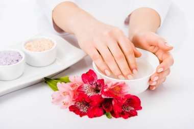 Partial view of woman taking nail bath with flowers