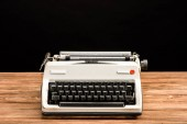 vintage typewriter on wooden table isolated on black