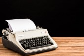 Fotografie vintage typewriter with paper on wooden table isolated on black