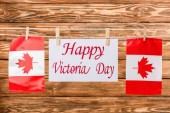 Photo top view of canadian flags and card with happy victoria day lettering on wooden background