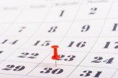 selective focus of red pin marking number 30 in calendar