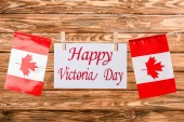 top view of canadian flags and card with happy victoria day lettering on wooden background