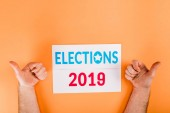 cropped view of man showing thumbs up near card with elections 2019 lettering isolated on orange