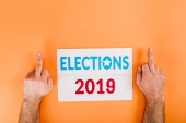 Photo cropped view of man showing middle fingers near card with elections 2019 lettering isolated on orange