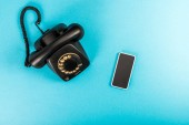top view of rotary dial telephone and smartphone with copy space isolated on blue