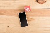 Draufsicht der Rss feed Icon und Smartphone mit leeren Bildschirm auf Holztisch