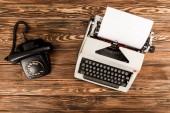pohled shora psací stroj a rotační telefon na dřevěný stůl