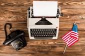 felülnézet írógép, rotációs dial telefon és a fából készült asztal amerikai zászló
