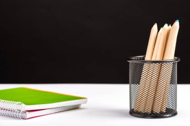 pencils and notebooks isolated on black with copy space