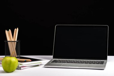 apple, notebooks, pencils and laptop with blank screen isolated on black