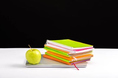 colorful notebooks, apple and laptop on desk isolated on black with copy space