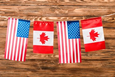 top view of canadian and american flags on wooden background
