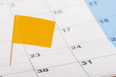 selective focus of yellow flag on number 22 in calendar