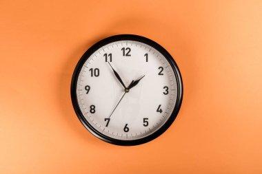 top view of round clock isolated on orange