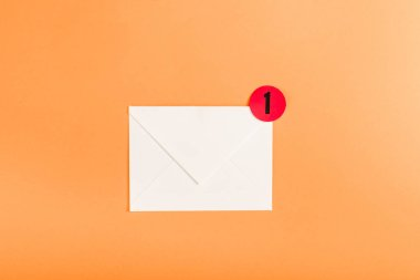 top view of paper envelope with red circle and notification with number 1 isolated on orange