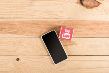 top view of youtube icon and smartphone with blank screen on wooden table