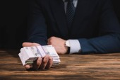 partial view of businessman holding russian rubles banknotes at wooden table