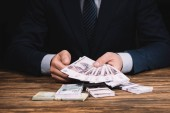 cropped shot of businessman in formal wear holding russian rubles banknotes above wooden table