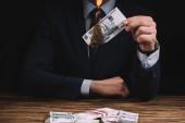 Oříznout záběr podnikatel hořící bankovek nad dřevěný stůl s ruských rublů