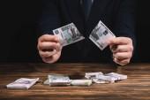 Teilansicht von Geschäftsmann, der Banknote über Holztisch mit russischen Rubel reißt