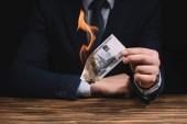 Střední část podnikatel hořící ruských rublů bankovek nad dřevěný stůl