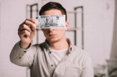 young man hiding face behind russian rubles banknote