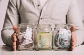 cropped shot of man holding glass jars with russian rubles banknotes