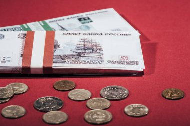 close-up view of russian rubles coins and banknotes on red