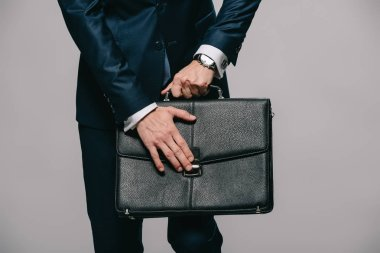 cropped view of businessman opening briefcase isolated on grey