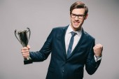 handsome businessman in glasses celebrating victory and holding trophy in hand on grey background
