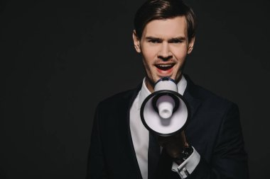 handsmome man in suit screaming in megaphone isolated on black