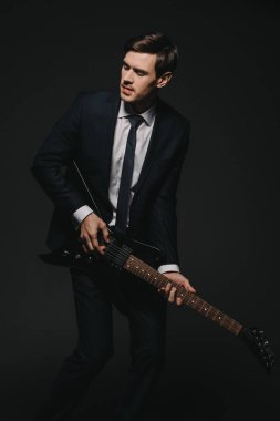 businessman in suit playing elecrtonic guitar isolated on black