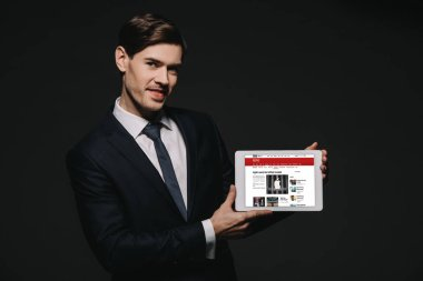 cheerful businessman holding digital tablet with bbc news app in screen isolated on black