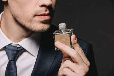 cropped view of man smelling perfume isolated on black