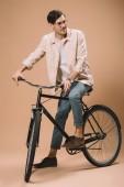 Fotografie veselý muž v brýlích jízda kole na béžové pozadí