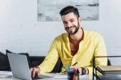 Vousatý podnikatel pomocí přenosného počítače, s úsměvem a při pohledu na fotoaparát