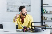 Usmívající se podnikatel drží tužku a koukal na dřevěné desce