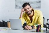 Pohledný podnikatel muž pomocí přenosného počítače, při pohledu na fotoaparát a usmívá se