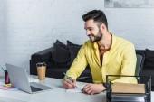 Usmívající se podnikatel pomocí přenosného počítače a psaní v poznámkovém bloku